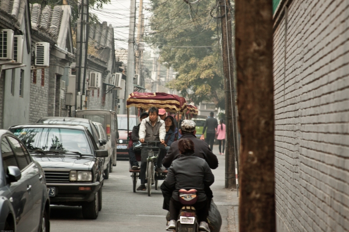 Rickshaw drivers pedal tourists through one of the disappearing hutongs of Beijing.