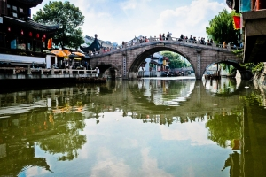 High, arched bridge spans the canal in Qibao.