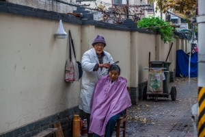 A woman gets her haircut on a Sunday afternoon.