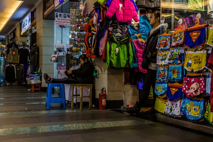 Young girl reads while mom works at a shop in Shanghai's underground AP MArket
