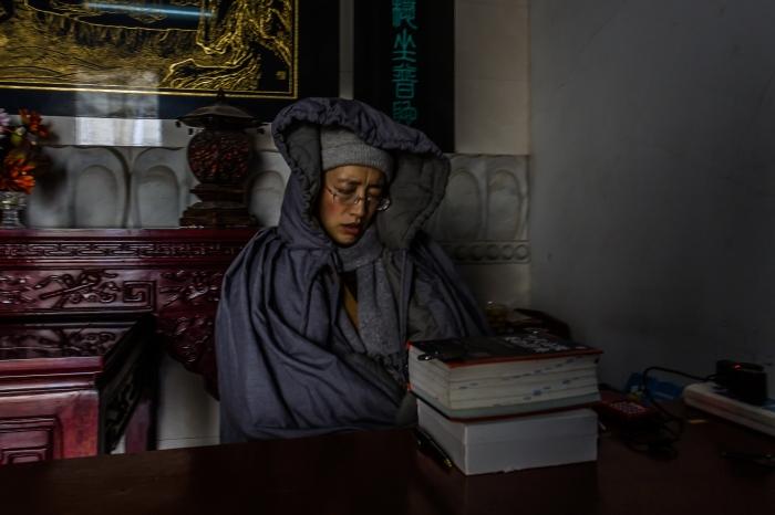 Nun selling tickets at entrance to Jimingsi Temple, Nanjing, China