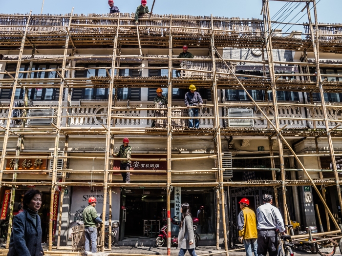 Workers construct a bamboo scaffolding in preparation for a building renovation project.
