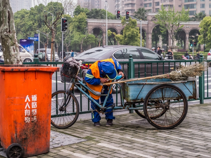 Street sweeper takes a break from his broom to fix the seat on his cart.
