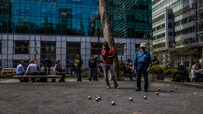 Competitors watch the final balls being tossed in a Bocce match