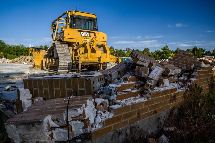 A bulldozer sits amid a pile of broken bricks  at the site of a former school, in Boise, Idaho, USA