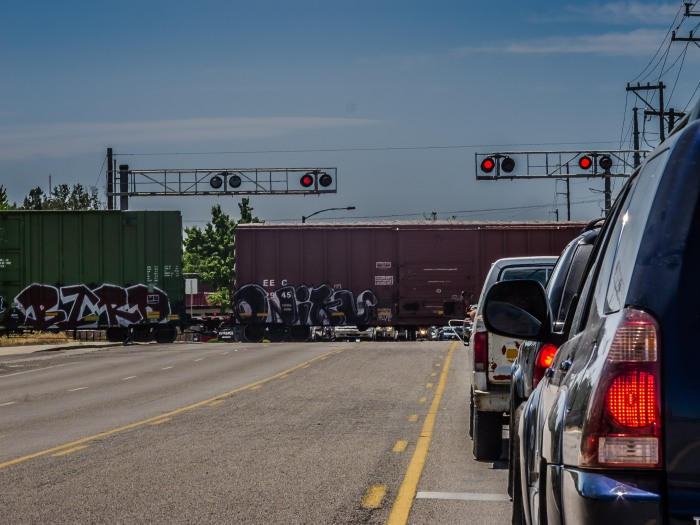 Traffic waits as a freight train crosses Curtis Avenue in Boise, Idaho