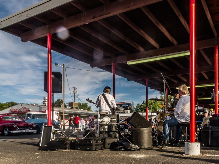A band plays classic rock & roll in the hot rod filled parking lot of Burger Time