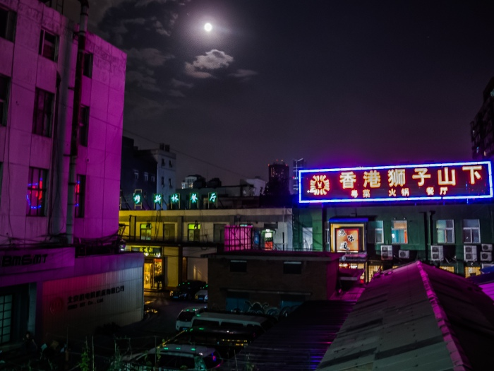 A full moon and neon lights illuminate a back alley in Beijing