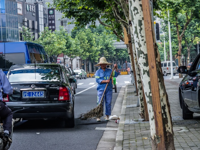 Impatient driver squeezes past street sweeper