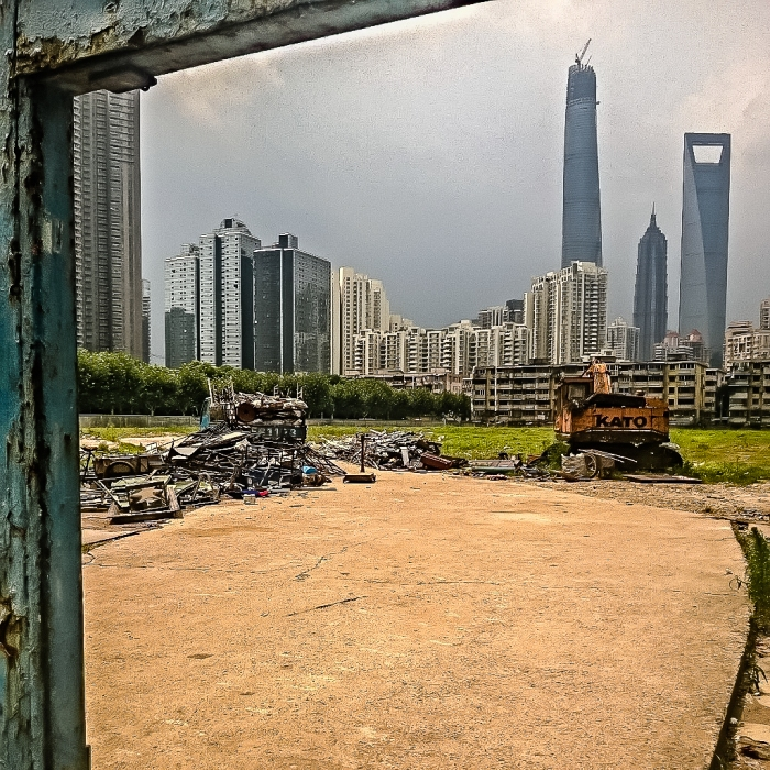 A recycling center operates on a vacant lot within view of two of the world's tallest buildings.