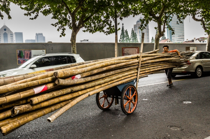 Worker delivers bamboo for construction of a scaffold. (Former French Concession, Shanghai, PRC)