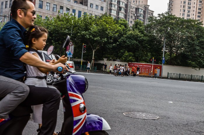 Three on a scooter is a common site in Shanghai.