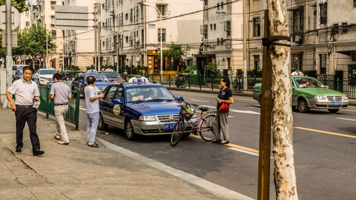 Bicyclist blocks path of taxi after minor accident; she is waiting for compensation