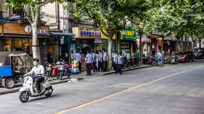 "China's ""chengguan,"" the para-police agency tasked with enforcing non-criminal urban administrative regulations, remove store fixtures blocking a sidewalk."