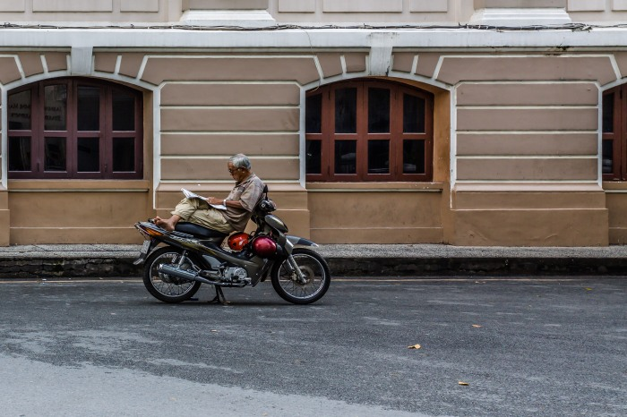 Man reclines on his scooter and reads his newspaper.