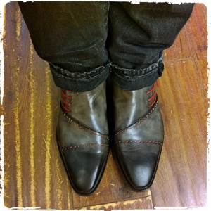Custom-made gray calfskin boots painted with black tips, red piping and laces