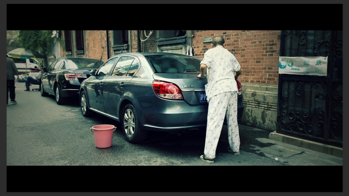 Man washes his car on a Sunday afternoon.