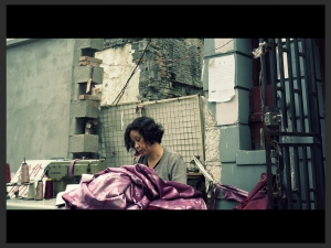 A woman sews curtains on a street adjacent to the South Bund Fabric Market, in Shanghai, China
